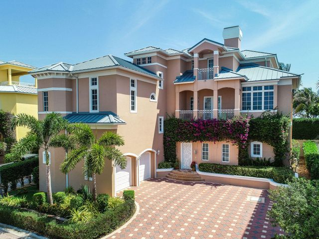 A truly unique beachfront offering in the seaside, gated community of Jupiter Key! Enjoy the sparkling Atlantic Ocean views and continuous breeze from multiple balconies and vantage points. This completely customized home features a private backyard oasis that is perfect for outdoor entertaining. A large pool and spa deliver a resort-style feel, while the extended loggia and outdoor fireplace offer plenty of areas for lounging or dining. A rare-find, this home has both a main house and a guest house allowing for optimal privacy and convenience. The main residence features an open gourmet kitchen, formal dining room, large master suite, guest suite and a private elevator. The grand family room has a built in bar,  an office and multiple balconies to enjoy the views. The guest house features 2 bedrooms and a bathroom and has direct access to the pool area. An additional home feature is the interior summer kitchen which is just off the loggia- allowing for ultimate comfort while cooking and an easy entertaining experience.     Right across from the beach and walking distance to the Juno Pier, this picturesque Key West style community is an amazing opportunity to live like you are on vacation. With three stories, four large bedrooms and a private backyard- this residence allows the ultimate comfort and convenience for a vacation or family home. Jupiter Key is a pet friendly community with pet friendly beaches just across the street. A stone's throw from all that Juno and Jupiter has to offer- pristine beaches, waterfront dining, shopping, golf and more!