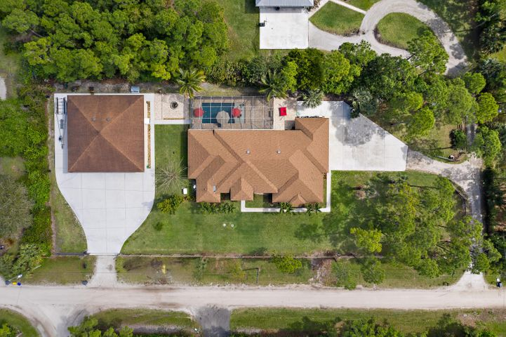 Impressive 2003 CBS home with a massive 50 X 50, 2500 sq ft, separate detached workshop with three 14'ft doors, on 1.25 fenced acres. The home is an open concept, split floor plan with 4 Bedrooms, 3 Bathrooms. The Master suite is extra large, with 2 walk-in closets and a nice ensuite. Large marble tile throughout the main living spaces, and laminate wood floors in the bedrooms. From both living rooms and kitchen overlook the 2014 saltwater pool that has a Baja shelf and is completely screened in. 2018 AC System, Whole house generator, Top of the line water system. Hurricane shutters for all windows. Partial Owner Financing available.
