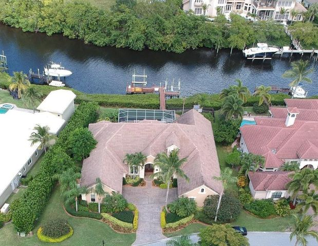This gorgeous waterfront pool home has sweeping river views with dock, 2 boat lifts and NO fixed bridges boasts 4 bedrooms, 5 full baths complete with paneled wood office, exercise room, 4-car garage & whole house generator.   Located in the upscale gated waterfront community of the Islands of Jupiter, this immaculate home offers lovely views of the Loxahatchee river. The beautiful screened lanai has a travertine pool deck, built in grill area and heated & screened pool for year round enjoyment. This Ruttenberg home features marble floors, crown molding, open kitchen, and family room separate living room and formal dining room. The Master suite is incredible with high detailed ceilings, large closets, a spacious master bath and beautiful river views. The 4th BR/Guest suite upstairs could The 4th BR/Guest suite upstairs could be a second master and has built in bar area complete with bar fridge and sink, separate sitting area and private balcony with sweeping river views.  The dock has 2 lifts (16K & 12K) w/ water and power at dock.  The whole house security/surveillance system can be easily viewed from a smart phone. Pets are safe and view unobstructed w/ invisible fence system.   Roof 2000 2017 Pool and patio were both resurfaced. Travertine pavers were installed on the patio and the pool was re-tiled.  2017 Pool heater and the pool was converted to salt system. Spa/Pool is also on remote control. 2017 New water softener system 2015 New Outdoor grill  2016 New Rinnai tankless water heaters 2011  (2) Boat lifts were installed  2018 Central Vacuum unit replaced 2018 Security system/cameras upgraded 2018 There are 3 A/C units in the house.  2 units downstairs and 1 unit for upstairs.  Both units for downstairs were replaced in 2018.  The Trane Unit upstairs is from 2012. 2019 New accordion hurricane shutters installed on large bay windows in master bedroom and large group of windows in main living room facing the canal.  2019 Hurricane impact glass upgrade installed o
