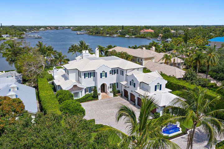 """Unrivaled craftsmanship is consistent throughout every inch of this breathtaking, riverfront estate. Its Dutch Colonial architecture separates this home from all the others with high-end finishes & amenities such as: imported European marble & hardwood floors; elevator; 5 gas fireplaces; state-of-the-art sound system throughout (plus 7 large flat screen TV's); media room with projection TV & 7 automated theater seats; gourmet kitchen with Calcutta Gold center island, Sub-Zero refrigerators & 60'' Wolf stove; butler's pantry with Carrera marble counter & sink, separate ice maker and wine closet; and grand, gated entry with decorative, cobblestone pavers that lead to a choice of 4 garages. Its outdoor living area is unmatched and boasts a spacious loggia, outdoor dining area, summer kitchen & sun deck, meticulously maintained backyard, salt water pool & with 100 ft. of water frontage, long views of the north fork of the """"wild & scenic"""" Loxahatchee River. The private dock with 2 lifts puts you just minutes away from the Jupiter Inlet. This well built & appointed home is a rare find like no other!"""