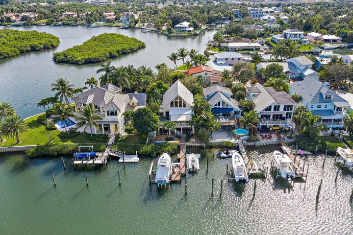 Best waterfront location in Jupiter with expansive views of Sawfish Bay and the Jupiter Lighthouse. This charming Key West style property features ''A frame'' construction providing soaring ceiling heights with dramatic exposed beams and tongue and groove ceiling detailing. Multiple docks will allow for up to a 60' boat with deep water access and no fixed bridges. Property has city water and sewer, but has no deed restrictions or HOA fees. Come live in your own island paradise.