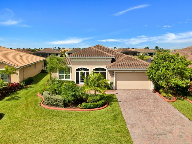 LOCATION, LOCATION, LOCATION!  This picture perfect KEY LARGO model has 2 MASTER brs with bath en-suites, 3rd BR with adjoining bath PLUS a DEN and is located in the heart of VITALIA, on the lake with a beautiful water view & it is steps away from THE CAPTIVA CLUB, a 24,000 sq. ft lakefront social clubhouse with state-of-the-art fitness center, ballroom with stage, social rooms, library, banquet & meeting room, billiards & darts, card room, tennis courts, pickleball, bocce, fire pit, pool &  putting green. This model perfect home has a gourmet kitchen with loads of cabinets & spacious granite countertops, walk-in pantry, SS appliances including DBLE wall oven & cook top, Plantation shutters throughout, COMPLETE HURRICANE IMPACT GLASS, screened patio overlooking the lake & screened entrance DBLE French doors to the den, surround sound system, extra sound proofing between the master suites and great room, extra insulation above the garage ceiling, pull down stairs to the attic access, epoxy garage floor, smart thermostat, ring devise at front door, professionally painted interior, upgraded fans in the great room, 3 bedrooms and den and it's wired for a whole house 17.5 kilowatt generator which is negotiable along with all the furniture AND the wall mounted TVS in the den and great room stay!  This truly is a picture perfect property & a very desirable 55+ community at Tradition where there is shopping, restaurants, services, hospital and lots of activity!  Whether it is at THE CAPTIVA CLUB in Vitalia or downtown at TRADITION, there are lots of activities, something for everyone!  This property is priced to sell so act fast.  You don't want to be disappointed!