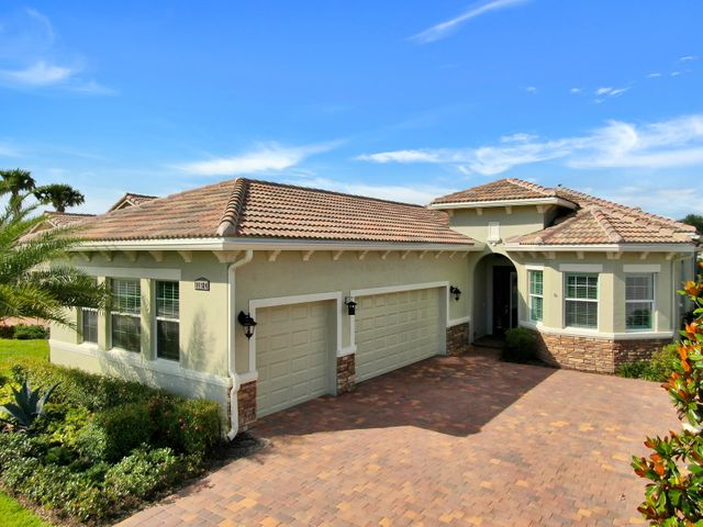THIS TRULY IS FLORIDA LIVING AT IT'S FINEST!  HUGE, FENCED YARD, 15'X9' COVERED PATIO WITH AN EXTENDED 12'X40' SCREENED LANAI BACKING TO THE C-24 CANAL!  Wait until you see the inside!  This beautiful property is model home perfect with all the current designer trends and finishes.  The kitchen will WOW you with the quality white cabinets, quartz counter tops, glass back splash, SS appliances including cook top, DBLE wall ovens, SS range hood, pot filler, TWO pantries & separate eating area overlooking the lanai & beyond to the private rear yard to the canal.  Additional designer finishes include porcelain plank floors, crown moldings, plantation shutters and powered blinds, french doors, quality light fixtures & fans, HURRICANE IMPACT GLASS THROUGHOUT & A 3 CAR GARAGE.. The master suite is lovely, light and bright with lots of closet space and a beautiful ensuite with upgraded cabinetry, quartz counter tops, spa tub and frameless shower enclosure.  The guest bedroom and bath are very private and the den is spacious and bright and overlooks the front yard and beyond to the lake.  Located in the heart of PGA Village Verano away from traffic, close to the new 27 court pickle ball facility and a short ride to Club Talavera, the 40,0000 sq ft club house with indoor & outdoor pools, spa, tennis, bocce, fitness, banquet hall, demonstration kitchen, arts & crafts, billiards, card room, bar/lounge, library, auditorium and huge patio with fireplace and a fire pit all overlooking the lake.  This is a spectacular home and community and one you don't want to miss!!!