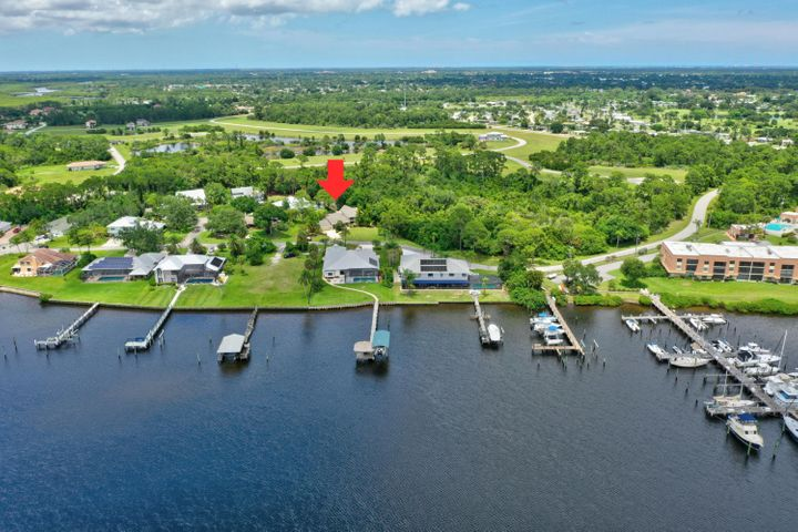 Bring the Boat! Enjoy the tranquility of this hidden gem of a neighborhood nestled on the St. Lucie River. No fixed bridges and a dedicated dock w/ electric & H2O w/ 6ft draught and can handle a 57' Sailboat. Only 16 homes in this tiny HOA with fees less than $1000 a year -- including your dock! This multi-level home has 4 beds, 3.5 baths with 2-car garage. Roof replaced in April 2020. Freshly painted interior and exterior in May 2020. Enjoy the open floor plan with the Cook's Kitchen and Family Room. Formal Living Room is a level below with a dramatic Oak Open Staircase and water fountain feature, fireplace and huge open windows. Slate floors on the main level. Fourth Bedroom can used for an Office, Den or turned into a second Master Bedroom Suite. The third level is  the huge Master Bedr Bedroom with space that can be used for baby room, home gym, office or private living room. Enjoy all the special touches  the Fireplace, The Fountain, the Rocking Chair Front Porch with St Lucie River, the Master Bedroom Balcony also with water views and with a nautical-wire railing. This is a great bargain for someone who wants immediate boat access without paying the high costs of being on the water. Across the street, homes on the water are selling for $1m or more.