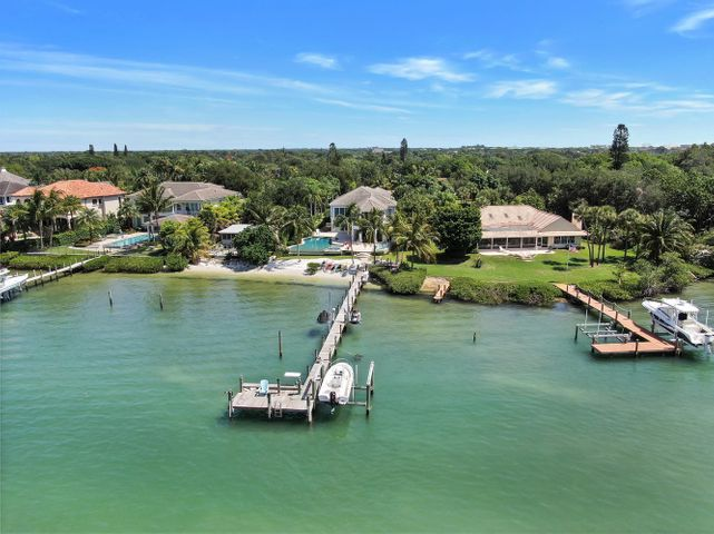 """Turquoise blue green water becomes your best friend at this magnificent riverfront home with southern exposure. This is one of the most desirable spots on the Loxahatchee River as you are able to sit on your dock and watch the turtles and dolphins swim right by. This two-story residence was redone in 2016 and boasts over 6,400 sq. ft. of living space, which includes 5 bedrooms, 5.2 bathrooms, a mudroom, and a kid's playroom on the 2nd floor. Engineered wood plank flooring throughout, gourmet kitchen, coffered ceilings in the living room, and pecky cypress in the family room. This home features soaring ceilings, solid core doors, a whole house generator, 1,000-gallon propane tank, impact windows and doors, and beautiful craftsmanship throughout. The large kitchen has Calcutta Gold marble honed on the island and backsplash, Sub Zero refrigerator, Thermador gas stove, U-Line wine refrigerator, double pantry and fixtures are Hans Grohe. The master suite boasts beautiful views of the river, walk-in his and her custom closet with built-ins, vanity area, and a spa-like bathroom with a large walk-in shower, dual sinks, White Diamond polished and honed countertops, Kovacs lighting, paperwhite Carrera honed and polished flooring.  Additional features of this home include 1 guest bedroom downstairs and the remaining guest bedrooms upstairs with plantation shutters and built-ins in the closets, marble countertops in the guest bathrooms. The lovely powder room features an Ann Sacks inspired mosaic glass design, 2 tankless hot water heaters, surround sound in the family room and patio area, gas fireplace controlled by a remote, CAT 6 wires in every room, security system, 4"""" high hats throughout, central vac, electric shades in the living room and bedrooms, and Hammer slate tile in the laundry room.  The residence is immaculate, with no expense spared.    Cool off in the heated salt-water pool, which has 2 new pumps or host a cookout with the outdoor summer kitchen, which features"""