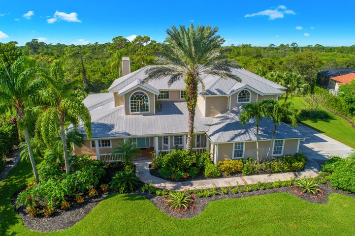 This sophisticated Key West Island-Style home, is located in the gated ocean access waterfront community of Bay St. Lucie. A private oasis, on over 2 acres, with lush tropical gardens and a natural preserve provide a paradise for indoor/outdoor living. A natural boardwalk leads to 303' of waterfront, a deep water dock equipped with water/electric, a fish cleaning station, and a mooring for a large vessel. Soaring ceilings and a spacious design provide for perfect entertaining family/friends. Overlooking the fenced in pool/spa, is a screened in patio, with a summer kitchen. This spectacular home features a formal dining room, a gourmet kitchen that will delight any chef, a wine cooler, a gas fireplace and plenty of built-ins and storage. The floor plan includes 2 owner suites, large walk-in closets, screened in porch, and a private balcony. With over 5,000 square feet and a 3 car garage there is plenty of storage. Being close to the Turnpike, I-95 and the Palm Beaches allows for easy commuting.  Projects underway, will be completed prior to sale: New 4 ft boardwalk with dual stringers to the dock, state of the art landscape lighting, and the exterior of the home is being professionally painted.