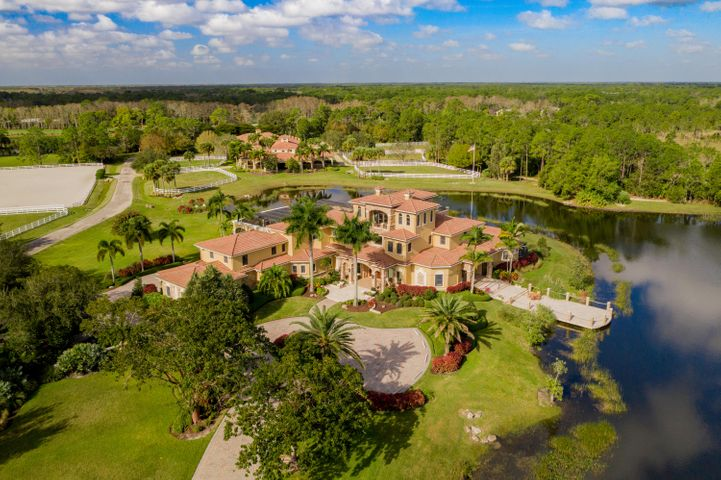 In the desirable gated community of Ranch Colony, sits one of southern Florida's most exceptional properties. This magnificent improved 30 acre estate lot includes a majestic Mediterranean-inspired residence overlooking a private four-acre fishing lake. The property features a heated saltwater pool, a guesthouse, currently an eight-stall barn that can easily be converted to many uses with living quarters, a riding and jumping arena, eight turnout paddocks, three turnout structures, and riding trails winding through cypress and pine trees. A 20 acre unimproved lot adjoins this property and can be purchased for $1,300,000.  These two lots are the subject of an approved subdivision plan.  Please contact the listing agent for more details. Highlights of the five-bedroom home include living and dining rooms, a chef's kitchen, a family and billiards room, a 1,000-bottle wine cellar, a luxurious ground-level master suite, and a lounge and terrace enjoying sweeping views of the property.  Home and main buildings are built at an elevation to eliminate flood risk with the highest hurricane impact construction standards exceeding Miami/Dade Hurricane Codes. Concrete and rebar poured roof and floor systems plus two commercial diesel generators provide for a safe, self-contained and secured property. This unique construction is found in less than 1% of the residential homes in Florida and represents a SUBSTANTIAL value versus replacement costs.  Ranch Colony is surrounded by nature preserves spanning more than 20,000 acres, affording access to parks and horseback riding trails. This property allows for great versatility. The stable can easily be converted into a second home or a common recreation/theater/entertainment center supporting additional custom homes on open land while maintaining privacy, the ultimate family compound.  It could accommodate a variety of activities and pursuits, e.g. space for tennis courts.  The highly adaptable barn structure is perfect for a studio fo