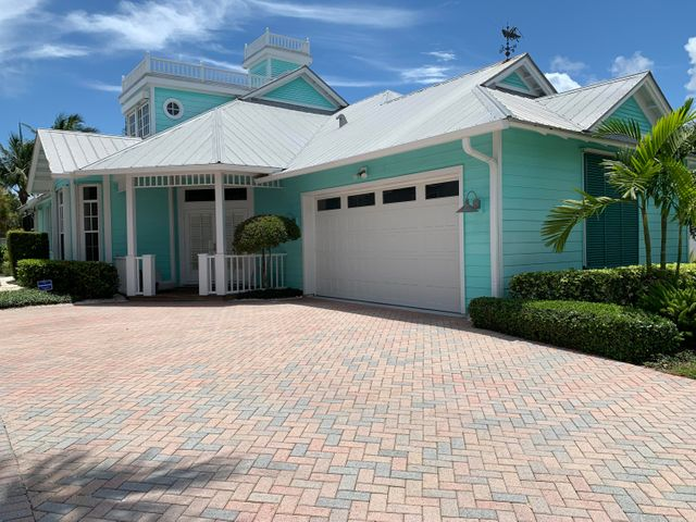 Rare opportunity to own a Key West style beach residence in the 16 single family home enclave of SEASIDE steps away from the sand of Juno Beach.  This custom built CBS block residence features Hardy- Plank exterior siding,  PGT windows, cypress covered porches, open floor plan with plenty of natural light, 10' smooth finished ceilings, hardwood floors, recently remodeled kitchen and baths, GE Profile stainless steel appliances, Grohe faucets, Kohler plumbing fixtures, Ashley Norton door hardware, oversized master closet, tons of storage, central vacuum, integrated baseboard pest control, security system, sleeved & insulated plumbing lines, water filtration system and a custom build-in pecky-cypress saltwater aquarium.