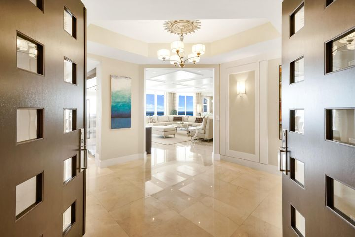 Sweeping panoramic ocean views can be yours! Step into luxury at this 22nd floor condominium at The Ritz-Carlton Singer Island Residences. From, your spacious, private terraces, enjoy sun-kissed views of the Atlantic and the Intracoastal. The floor plan of this luxe residence offers a 3BD/3.5BA plus a den and formal dining room. Oceanfront opulence abounds in this condo including a private elevator foyer with custom double door entry, 9-foot 4-inch ceilings, polished Crema Marfil marble, exquisite ceiling and wall work, and opulent stonework. A beautiful gourmet kitchen, custom Italian cabinetry, and scenic floor-to-ceiling impact glass sliding doors add to the sumptuous feel of this home. The kitchen features a large granite island with wine cooler, Wolf gas cooktop and oven, Sub-Zero refrigerator, and a Miele coffee center. Relax on your private balcony and take in the panoramic ocean views or partake in all that the Ritz-Carlton Singer Island Residences has to offer, including an oceanfront lagoon-style pool, a poolside resident restaurant, cinema-style theater rooms, and more. The Ritz-Carlton Singer Island Residences is situated on 8.8 acres of private, pristine beach at the southern end of desirable Singer Island. Other amenities include 24-hour concierge service, valet parking, two state-of-the-art fitness centers, boardrooms, a poolside summer kitchen, a library and an oceanfront lobby. This residence is offered with two adjacent parking spaces and extra storage.