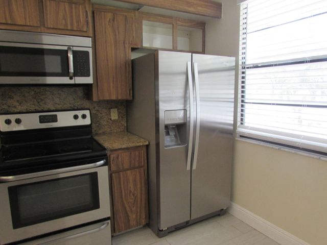 Beautiful Whitehall Community,Corner Unit, Great location, convenient to Banks, shopping and more. Between I95 and the Turnpike, close to the beach, 1385 sf, nice size rooms.  Strorage room 10x10 could be office, den. Stainless steel appliances 2 pools and clubhouses.  All tile flooring and a pet is allowed 20lbs or under. AC 3 years old, kitchen appliances  4 years old,,updated master bath. Freshly painted and cleaned ready for move in,  A rated schools. Small golf course view. Vacant and ready for a quick close,  Come make this your home today,Florida living at its best,  Assoc requires 20% down.  A rated schools!