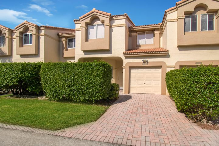 Luxury lakefront townhome with attached garage, in exclusive gated Boca Raton community.