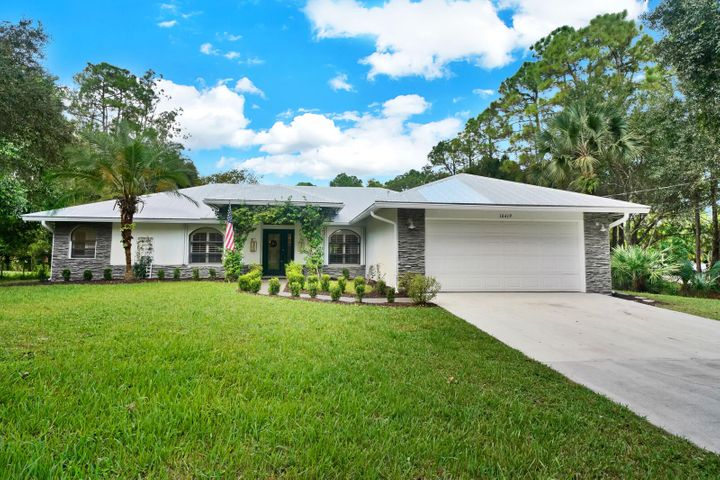This beautifully renovated CBS home includes 4 bedroom 3 full bath's on 1.25 fully fenced acres in beautiful Jupiter Farms. The home renovated in 2016 and includes a separate office/playroom and separate formal dining room. Brand new metal roof (2016), all new landscaping including several fruit trees, engineered wood floors throughout the entire home, shiplap in kitchen and dining areas, designer light fixtures. Huge chefs kitchen with vaulted ceiling and high end, professional DCS appliances, drawer microwave, RO system and huge farmhouse sink, white shaker cabinetry, butcher block and quartz counter tops, open exposed shelving and large custom hood for a farmhouse vibe. New water softener system. Barn doors lead you into your expansive pantry room/ breakfast nook & TONS of storage!..... There is a seperate laundry room with front loading washer dryer and 2 car garage. Custom closets in bedrooms including his & hers large master closets. Living room boasts a shiplap wood burning fireplace and dual sliding doors leading you out to the covered lanai/pool area. Backyard features chicken coop with fenced garden area and children's playground. Home security system with indoor and outdoor cameras. Underground propane tank powers gas range and oven. Accordion hurricane shutters. Some furnishings negotiable.