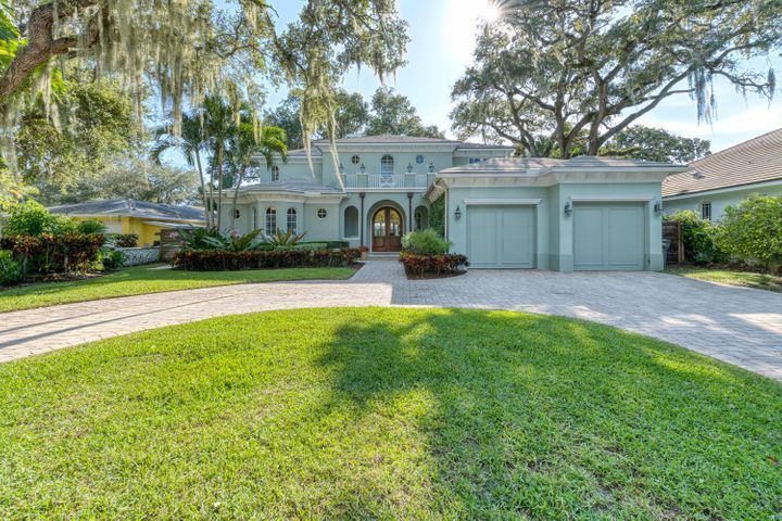 This Stunning Custom Built Waterfront Home is only 2 lots from the Intracoastal Waterway! Along with 85' of waterfrontage and a 65' dock with 12,000lb. lift, this Home is beautifully situated on a lush tropical landscaped 1/2 acre lot and framed by 3 mature Live Oak trees. Desirable features include impressive Mahogany & Glass Arched Front doors lead into a bright and spacious open floor plan, soaring volume ceilings with crown molding, saturnia marble & hardwood floors throughout, impact windows & doors, water views from almost every room. 1st floor master suite with access to covered lanai and pool. 2nd floor master opens to large balcony overlooking pool and waterway! Plus 3 ensuite bedrooms and two additional 1/2 baths. The large wrap around covered Logia has tongue and grove ceilings  and a summer kitchen with plenty of outdoor living space. Perfect for your outdoor entertaining! Tropical pool and spa finish off this beautiful backyard! Other features are a Coral Stone Gas Fireplace, wine closet, open-concept chefs kitchen with a 6 burner Gas Range with double ovens, SubZero fridge, a warming drawer, 2 SubZero beverage drawers,Miele dishwasher, insta-hot faucet, pot filler, wine fridge, large pantry, granite countertops and a breakfast bar & dining space. 2 car garage with lift, central vacuum, 500 gallon propane tank.