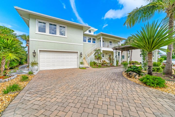 Steps away from the white sand of Juno Beach sits this Key West style home. A modern home with a bungalow feel, this 2011 home features impact glass, xeriscaping, and a widows walk with 180 degrees of blue ocean. Pull up to the Jasmine covered pergola and enter into the foyer of your new home. First floor features a kitchen and living area complete with an electric fireplace and ceilings soaring to the second floor. 4 windows with electric shades. On the second floor you'll find the main living area, owner's suite, guest bedroom and full bath and tucked away is an office with a closet. Up the spiral staircase you'll discover a sanctuary flex room with ocean views and its own balcony. As an added bonus, the first floor features a separate 1 bedroom guest home with its own entrance, laundry, kitchen, living room and bedroom. Walking distance to the ocean, Juno Pier, shopping and restaurants.
