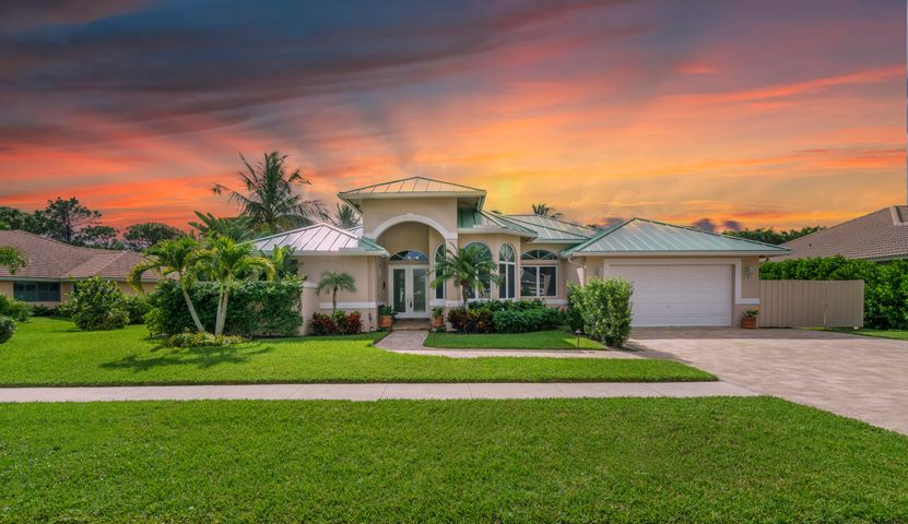 Enjoy a luxurious Jupiter lifestyle in this wide-open floor plan with up to 15 ft. souring cathedral ceilings. 3BR, 3BA, OFFICE, LR, FR, DR, Nook. LOW Martin County Tax & Insurance & HOA fees, NEW 2018: standing seam metal roof; (2) A/C units; hardwood flooring.  NEW 2019: 3 vehicle wide paver driveway; GE microwave & GE stove; landscaping; landscape lighting; irrigation system; fence/gate; garage opener motor; pool pump; pool timer; pool salt generation system.  NEW 2020: Re-grouted pool tiles; stained pool deck; light fixtures, faucets, hardware & paint in cabana bath & guest bath; interior and exterior doorknobs and locks; master bathroom totally renovated with white cabinets, quartz countertops, designer faucets, exquisite lighting; Garage floor was epoxy paint & walls painted white. Enjoy a luxurious Jupiter lifestyle in this wide-open floor plan with up to 15 ft. souring cathedral ceilings throughout the master bedroom, office, living room, family room, dining room, breakfast nook, and kitchen - all with sliding glass doors leading to the pool/spa & lanai.   The Master Bedroom Suite offers lots of privacy, huge walk-in closet, linen closet and convenient sliding glass doors leading out to the pool area for that midnight swim. The master bathroom has a soaking tub, large separate shower, 2 beautiful vanities with a tropical / orchid atrium view. The large master bathroom was totally renovated with white cabinets, quartz countertops, designer faucets, exquisite lighting in Oct 2020.   New A/C units (2) in Apr 2018; New hardwood flooring in Apr 2018; New standing seam metal roof in Nov 2018; New gorgeous paver driveway, New GE microwave & GE stove, New landscaping, New landscape lighting, New irrigation, New fence/gate, New garage opener motor, New pool pump, New pool clock, New pool salt generation system... all in 2019; Re-grouted pool tiles and stained pool deck in Sept 2020; Cabana bath and guest bath were updated with new light fixtures, faucets, hardware & 