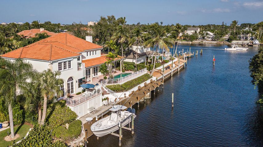 A Boater's Dream in the heart of Palm Beach Gardens with a 100ft deep water dock perfect for a large boat. Dock also has 12,000lb boat lift and 2 storage tackle rooms. Enjoy a 6-mile ride to the Palm Beach or Jupiter inlet, NO fixed bridges. This Mizner-style 4 bedroom, 4 1/2 bath, plus office, sits in front of a private Nature Preserve at the opening of the Intracoastal waterway. Located in the sought after Gated community of Bay Village off Prosperity Farms Road.  You will be just 20 minutes from the Palm Beach International Airport and minutes away from The Gardens Mall, Marinas, Restaurants and Gourmet Markets. A freshly renovated kitchen with views of the Intracoastal waterway complete with a sub-zero fridge/freezer and all new appliances. All impact glass and spacious 3 car garage.