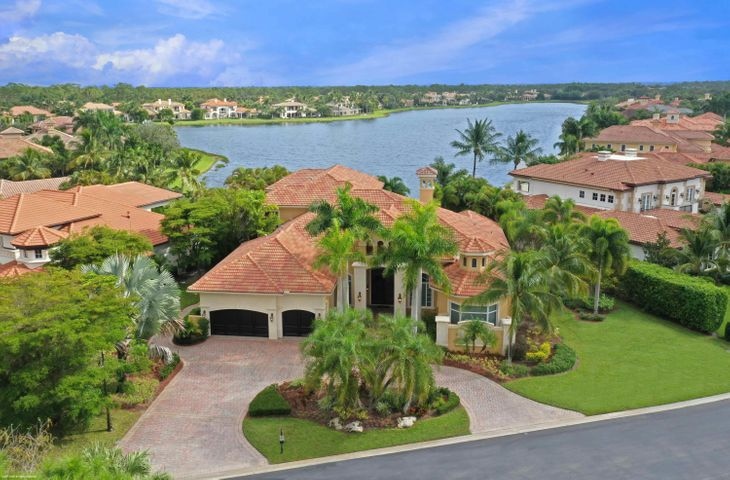 Panoramic water views from almost every room in this 5 bedroom, 6 full and 2 half bath one-of-a-kind custom estate home in desirable Mirasol.  Downstairs open floor plan with long lake views begin as you enter through a high ceilinged foyer that flows into an impressive living room with fireplace, dining room, wet bar, family room, kitchen, butler's pantry  and  breakfast area.  The newly installed custom kitchen has quartz countertops, decorator designed cabinetry, two sinks, two dishwashers and Viking, Bosch and Subzero appliances.  Additional downstairs features include Robert Abbey and Corbett light fixtures, coffered ceilings, powder room and marble flooring.  The main floor continues with a luxurious master suite with a sitting area overlooking the water from the wrap around... windows, his/hers bathrooms, large closets, dressing area, and breakfast bar.  There are two additional guest bedrooms with bathrooms and a wood floored office with custom built-ins.  The second floor has a large wood floored loft area and two full guest suites that all have access to the upstairs deck through large sliding glass doors and the most amazing lake, Mirasol and sunrise views.  The upstairs is completed with a private theater room with an Epson ProCinema 4050 projector, a powder room and a wet bar.   Outdoor amenities include a summer kitchen, covered patio with phantom screens and a large pool and spa with unmatached private unobstructed wide lake views. True 3-car garage w/additional golf cart garage.