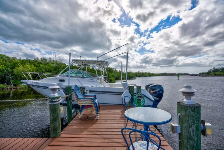 Spectacular views of the Intracoastal Home with a 12 K# Dock fits up to a 34 ft Boat. The Home has an addition over 900 sq ft build in 2017. So much room for a Pool with the extra Large lot.  Totally remodeled with hardwood floors, New Appliances and Granite. Other New Features Impact Windows and Doors, New Garage Door, New Hot Water Heater New AC. Master Bedroom has New Sliders to capture the view of the intercoastal. For the Outdoor Living enjoy sitting in the New Spa looking out at the intercoastal. After a Day of Boating there is a HOT and Cold Outdoor  Shower to refresh yourself. The Landscape is Beautiful.