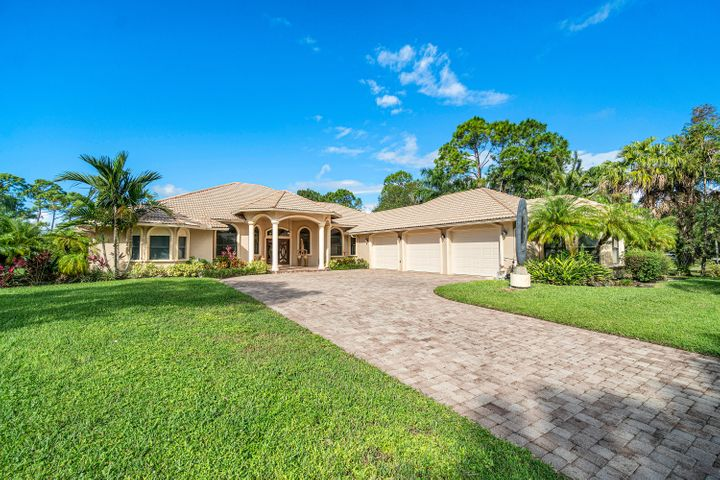 Arrive home with pride to your custom built 2005 Mediterranean designed home with 4,111 sq ft of living space featuring 4 bedrooms, 3 baths, CBS construction & heated pool with waterfall located on the 1st hole of Jonathan's Landing Old Trail Golf Club in Jupiter Florida. Nestled on 1 acre with magnificent Silver Bismarck Palms and space for vegetable garden. Immaculate & meticulously maintained this home features high impact windows and doors, new artisanal wood and glass front doors, vaulted tray & sloped ceilings, fireplace, 20'' tile, new carpeting, interior freshly painted, abundance of space for entertaining, crown molding, large chef's kitchen with cherry cabinets, granite counters, walk in pantry and center island, The 3.5 garage has 2,456 sq ft of storage space for all your need Foyer with tumbled marble tile border. Illuminated tray ceiling in living room entry. Pool safety fence added when original screen enclosure removed. Remote controlled screened patio added by seller but needs connection to electric to finalize. Outdoor shower, additional covered patio by back door in family room, uncovered patio also available. Silver Bismarck Palm Tree added by pool. Two zone A/C, 80 gallon electric water heater w/circulator, instant hot in primary suite, brand new Kenmore front loading washer and dryer, brand new Frigidaire cooktop, GE Monogram exhaust hood, refrigerator/freezer, wall oven and microwave. Surround sound speakers in family room. Monitored alarm ADT system. Zoned irrigation with well water and septic tank. Pull down attic steps in garage. Attic re-insulated in 2018. New water pressure tank. Roof, home and brick pavers professional cleaned November 2020. Built in 2005 by Genesis Custom Home Builders of Jupiter FL. Membership to Jonathan's Landing Old Trail Golf Club is not required nor included. Dryer vent cleaned when installed. Road resurfaced 11/17/2020. Currently installing Hotwire Communications.