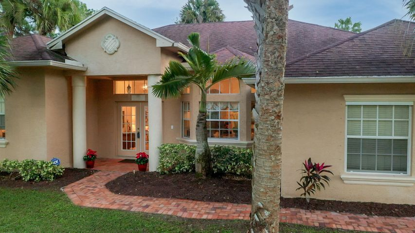 From the moment you arrive at this beautifully landscaped yard with mature palm trees, you will be aware of the serenity present.  The free-form pool and spa on the pavered pool deck allow for lazy afternoons in the private yard.  Inside this 4/3 home is spacious with plenty of light from the large windows: bright and open feeling, formal dining, separate family and living rooms.  Tile and laminate wood floors, granite countertop, stainless appliances. Wood fence, sprinkler system, an extra long paved driveway and front walk provides plenty of parking space for your guests and family.