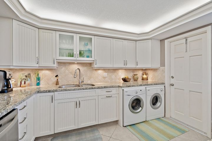 This beautifully renovated condo is located in the highly sought after Barclay development, a quiet oceanfront 55 age and up development in Juno Beach! This perfectly situated unit is just steps to the private beach & has a beautiful view of Pelican Lake! The updated kitchen features white cabinets with soft-close drawers, under-cabinet lighting, beautiful granite countertops and stainless steel appliances. Diagonal Tile flooring throughout and both bathrooms have been renovated with granite countertops and tile-surround showers. The Owner's Suite has a large walk-in closet with built-in cabinets. The HUGE enclosed balcony with peaceful views of Pelican Lake is accessible from the spacious living room & the owner's suite. Furnishings negotiable. Assigned carport.Washer & Dryer included!