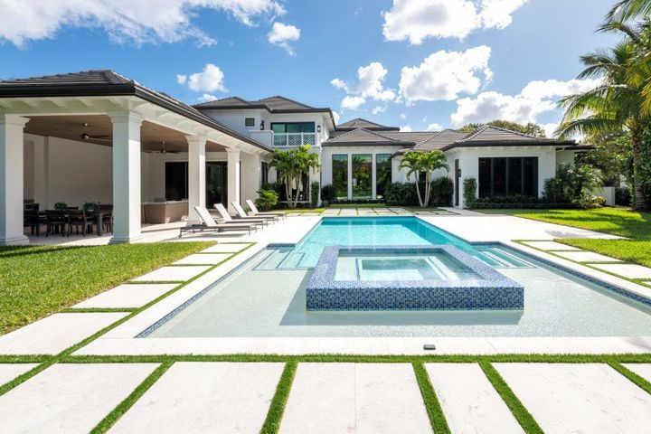 This impressive residence was built in 2019 by esteemed builder Courchene Development, w/ superb details implemented by luxury designer Insignia Design. This unique property is offered with a RARE TENNIS membership and is located on a cul-de-sac on one of the most private streets in Admirals Cove, enabling a quick walk or golf cart ride to the courts or the 1st tee, clubhouse or your boat (on site marina slips are available!). Oversized lot (.64 acre) expansive front & back yards as well as coveted extra parking & breathtaking curb appeal. Exquisite detail & impeccable design is found in this transitional West Indies property offering a combination of warmth & function. This 4 BD/6 BA residence with home gym (potential 5th bedroom) and a split floor plan entailing 7,730 LSF/10,800 TSF. Upon entering the grand foyer, you are greeted with soaring 14 foot ceilings and breathtaking design at every turn. The open floor plan invites entertaining, with a custom bar, marble floors and timeless living and family room area. Enjoy preparing meals in the gourmet kitchen with professional grade appliances, complete with butler's pantry and large walk-in pantry. View the latest movie or watch your favorite sports team in the oversized theater with luxury seating for 10.  Exercise at your convenience in the stellar home gym complete with multiple cardio machines, free weights and AXT-5 deluxe. Work from home in style with his and her separate offices complete with custom cabinetry.  The serene master bedroom wing defines style with spacious his and her walk in closets and luxurious separate full ensuite baths. Enjoy holidays and events in the formal dining room with exquisite details. The custom staircase leads to a versatile, large loft area complete with kitchenette and beautiful balcony. Adjacent to the open loft are two spacious bedrooms each with full ensuite baths. This property has meticulous internals with custom air purification, new HVACs, state of the art generator, imp