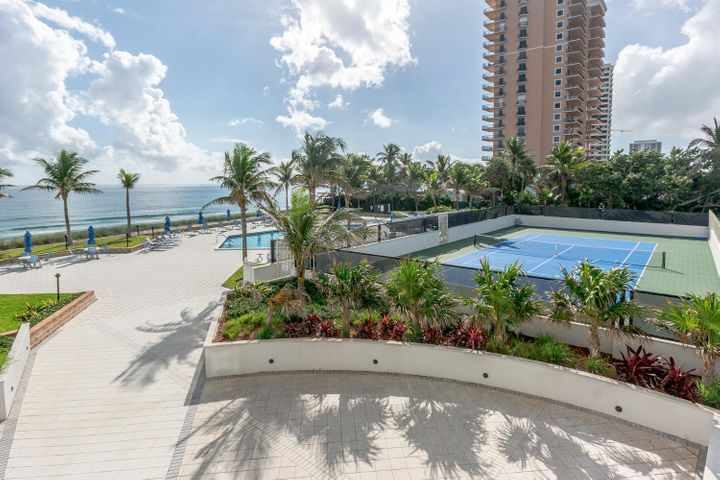 The perfect beachfront condo. Large 3/3 with Southeast exposure overlooking the ocean,  Enjoy sunrise from this large over size balcony. Updated with tile and carpeting. Formal dining room, eat in kitchen. washer/dryerImpact windows and doors. Gated assigned garage parking.  Tennis court, summer kitchen,storage for paddle boards, beach chairs.New lobby, excercise room