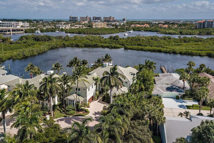 The Harbour is a petite but grand community within Jonathan's Landing! Grand and sophisticated this spectacular five bedroom, four full and two half bath waterfront home has incredible views of a large lagoon with direct access to the intracoastal waterway. Walk through the front doors and you will immediately see the breathtaking beauty of the custom-built home. The main level includes a grand two-story foyer with a sweeping spiral staircase, large dining room, formal living room with a beautiful two-story fireplace, family room,  bar area, large bedroom with private bath, office, gourmet kitchen with breakfast nook, and sweeping waterfront views. The second level, with elevator access, has 4 bedrooms and 3 bathrooms. The large master suite with a spectacular master bathroom and closet  area and a private balcony that overlooks the outdoor living area and lagoon. To help round out this gorgeous house is an incredible outdoor living area with retractable screens, a resort style pool/spa, tile patio, summer kitchen with cabana and an outdoor shower. Two car plus golf cart garages, with plenty of storage.  Included in the home are two deeded boat slips, one with a 18,000 pound lift and the other that can accommodate up to a 70 foot boat. Easy in and out deep-water access to intracoastal and no fixed bridges to the Jupiter Inlet and Atlantic Ocean.