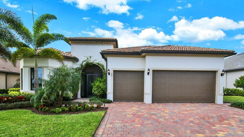This DiVosta built one story home is located in a quiet gated community in Jupiter, a short drive to beaches, golf courses, restaurants, shopping and airport.The covered screened entry opens to an open concept split floorplan with a neutral color palate to fit any decor.  Off the foyer,  glass French doors lead to flex space that could be used either as a home office or den. The gourmet Kitchen has Kitchenaid stainless steel appliances, upgraded cabinets, granite countertops, subway tile back splash and a huge center island that comfortably seats 4. The light filled dining area has zero corner sliders that open up to the covered lanai. The 20' x23' Great Room has 11' coffered ceilings w/ crown molding, is perfect for small family gatherings or entertaining a large group of friends. The beautiful wood-look porcelain tile extends from the house out onto the lanai, seamlessly connecting the outside in. (Lanai also has footing and gas line and is permitted for gas fireplace with stone surround at extra cost to buyer.) The remote control motorized screen opens onto the private lushly landscaped yard, with free-form saltwater pool and spa, summer kitchen, outdoor shower, and a view of the lake and preserve that you have to see to believe. Have a cocktail sitting on the built in bar stools in the pool and watch the sun setting behind the palm trees, and you will feel like you are on vacation all year long. The enormous owner's' suite with 11' coffered ceilings, master  bath with soaking tub & shower with frameless glass, double sink vanity and large WIC.  2 additional guest bedrooms, and 2 full baths, laundry room, 2 car plus golf cart garage complete this home. With Impact windows, and full house 22K generac generator this home has it all and more.  Expansive Community clubhouse with on site property management, mailroom, fitness room, activity room, community room, kitchen, Tennis & pickleball courts, playground, Resort style pool and spa with BBQ grills and gas firepit 