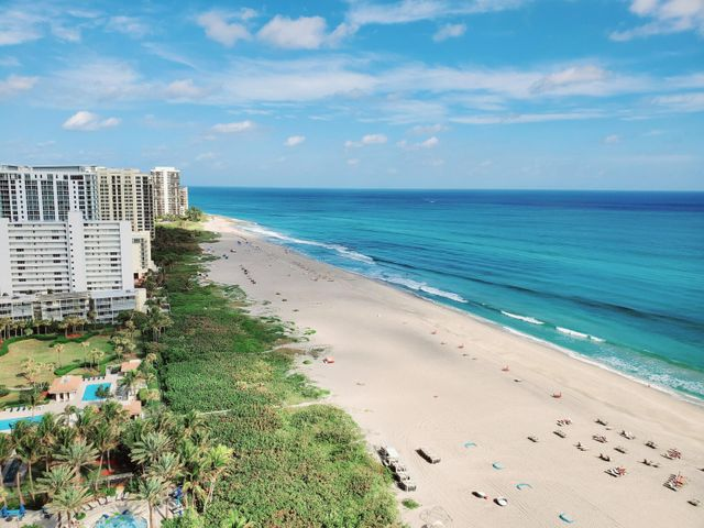 THIS VIEW! One floor from the top! Enjoy amazing sunrises & panoramic ocean views in the highly coveted BEACHFRONT Happiness Tower. This 18th floor retreat is in a premium location, just behind direct oceanfront. Pre-wired for smart home customization, this luxury residence offers modern design features in an open concept setting. Sleek kitchen, with custom European cabinetry, quartz countertops, Wolf & Sub-Zero appliances. Imported Italian porcelain flooring, spacious walk-in closets, laundry room with full size washer/dryer. Expansive windows and floor-to-ceiling sliding doors, all with hurricane impact glass. Relax with a glass of wine on your private 40 FOOT TERRACE, featuring   glass railings for unobstructed views of the sand & sea. 182 residences on 300ft of prime Island oceanfront. Amenities include controlled access elevators, 24/7 security & lobby front desk, valet, electric car charging stations, four food & beverage options, state of the art Fitness Center, Pilates studio, private training rooms, 56,000 sqft Wellness Spa with 22 treatment rooms, 2 couples suites, whirlpool, yoga terrace, meditation garden, private card room, private social terrace and bbq area, social room with bar, catering kitchen, billiards and entertainment overlooking the heated pool. Beach and pool services with attended cabanas, towels and umbrellas. Dog friendly, including a dog walking area. 155 hotel rooms for visiting guests, with resort housekeeping and room service available to the private residences. Elegance & sophistication, with an emphasis on Health & Wellness. Amrit Ocean Resort is a collaboration between global spa innovators and the Himalayan Institute, a renowned authority on holistic health. Nothing else like this exists on Singer Island! **Photos of the beachfront are from the balcony of the actual unit. Completion Spring 2021** Data and measurements deemed reliable but subject to errors, omissions and changes. Buyer to verify with Developer.