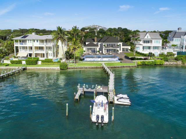 Fantastic opportunity to build your dream home on the magnificent blue water located in a no wake zone with panoramic views of the Intracoastal and the famous Jupiter Island! Start fresh and create your own waterfront mansion and claim over 100ft of direct water frontage. Only minutes from the ocean and nestled between $15M and $10M homes with private beach and 100+ ft dock with multiple slips for an 80+ ft. boat. This is one of the most desirable locations in Jupiter as its located directly across from the prestigious Jupiter Hills. Enjoy the waterfront lifestyle while paddle boarding, fishing, boating (House in photos are renderings and not on property) Not looking to build? No problem! The existing 8 bedroom, 7 bath home is located in Martin Co. with panoramic views of the Intracoastal