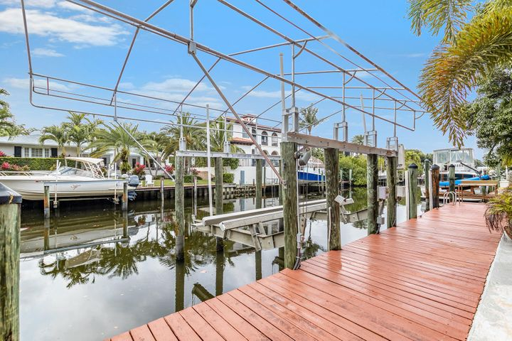Boaters- stop paying for storage + get back to the salt life w/ this 4 BR house with a private dock, 18,000 lb covered boat lift, 80' of water frontage and direct ocean access via Intracoastal waterway canal. No HOA. Garage has electric car charger for electric cars like Tesla! 4BR/31/2BA waterfront home has a large screened in patio + authentic tiki hut w/ a bar. Semi-circle driveway + 2 car garage offers room for outdoor gear, hobbies + your car. Features of this one story open floor plan home include a modern high-end kitchen w/ ample counter space for chefs or social gatherings overlooking the canal, laundry room w/ full size W/D, full hurricane impact windows AND a 20KW whole house generator.