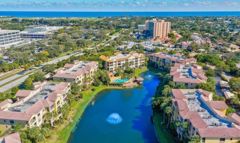 Enjoy Florida Living at its finest in this Tropical Paradise! Spectacular 4th floor unit with southern exposure overlooking the lake! Beautiful Porcelain Tile Floors & Crown Molding in the main living areas! Gated Community has 2 pools, w/jacuzzi tubs, fitness center & picnic area w/outdoor grill! Minutes from the Beaches, Boating, Golf, Downtown Gardens & Restaurants! Unit comes with 1 covered parking space #35.  Make this lovely condo your home or a great 2nd home! Seller may consider selling the furnishings.....ask agent for details!
