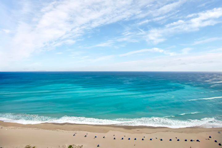 Skyward serenity is yours in this spectacular 34th floor Riviera Beach residence with stunning sea views, and amenities second to none. Soaring high above the exclusive seaside community of Singer Island, this 2-bedroom, 2-bathroom condo sits near the top of Tiara - a towering pinnacle of luxury and design, entirely rebuilt to the latest codes after recent hurricanes. Here, the views are unavoidable thanks to expansive balconies on each side of the residence - surrounding you with over 180 of Island and Atlantic vistas. Both bedrooms include balcony access and unobstructed views. And, on the 34th floor, you'll be high enough to guarantee those views forever - even as other (shorter) condos are built nearby. When you tire of gazing at the beach from your private balconies, you can enjoy it firsthand at Tiara's private beach access. In addition to this, the building features top-tier resort amenities  like its 24-hour guarded gate and dedicated concierge, poolside snack bar, beachfront restaurant for dine-in or delivery, and its world-class restaurant/lounge on the 46th floor with mind-blowing, 360° views of the ocean and intercoastal waterway. The pool is heated, with a separate jacuzzi. Its cutting-edge men's & women's fitness centers include a steam room & sauna for you to work up a relaxing sweat. Keep up your active lifestyle on the tennis court  or keep it low key in the building's unique library, billiard room, or card parlor. There's even an available 1-bedroom suite in the building  designed especially for guests of Tiara owners.  Back at home, perched above it all, you'll enjoy the effortless flow of your private residence. Its kitchen is wrapped with abundant granite counter space and premium cabinetry, with stainless-steel appliances and access to the balcony, just steps away. The sky's natural daily light shows are available in every room  each of them offering a nearly panoramic view of pure Florida enchantment. Your HOA fees include building insurance, water, trash collection, and basic cable with DVR and WiFi. From your high-rise home, you'll be incredibly close to some of Palm Beach County's finest shopping and dining destinations  and just 25 minutes from PBI Airport.  Call today to arrange an in-person or virtual tour of this private oasis in the sky.