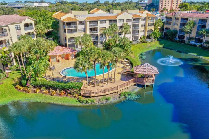 Spectacular corner unit overlooking the lake with plenty of natural light! Tile floors throughout to include the screened in balcony! Beautiful granite counters in kitchen & bathrooms! One covered parking space is included in the purchase. Gated Community has 2 pools, w/jacuzzi tubs, fitness center & picnic area w/outdoor grill! Minutes from the Beach, Boating, Golf, Downtown Gardens & Restaurants! Enjoy Florida Living at its finest in this Tropical Paradise!