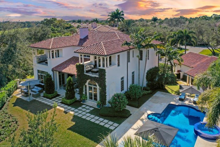This spectacular light and bright estate home offers a spacious floor plan located in the prestigious Trump National. The estate offers a separate 2bd/2.5 bath guest house with living room, laundry, and preserve views. This custom built home boasts 7 bedrooms and 7 1/2 bathrooms, along with a 4 car split garage with one space being air conditioned. Walk in the welcoming entryway leading to a light and bright sitting room with fireplace and backyard views. The family room has stunning custom built-ins for the perfect entertaining space. The crisp white eat-in kitchen offers top of the line appliances, including Sub-Zero refrigerator and gas range. Enjoy your morning coffee with beautiful views of the lush greenery from the large kitchen bay window. Stay in and enjoy movie nights in the well appointed home theater, featuring comfortable leather chairs and oversized media screen. Retreat to your luxourius primary bedroom suite with newly refinished wood flooring and custom fitted closets. Step outside your bedroom and relax on the private balcony and enjoy the views. The primary ensuite offers dual vanities with new porcelain countertops, jacuzzi tub, and large glass walk-in shower. The den/office offers custom built-ins and double french doors bringing plenty of natural light to the space. Step outside to your own private retreat. The beautiful backyard offers a sparkling custom pool/spa featuring new tile and coping. Relax under your covered patio, or move to the newly designed sitting area under a custom built pergola. New electric screens have been installed off of the living room and breakfast room. Gather around the outdoor fire pit on chilly evenings.  This property boasts the largest lot on the street and also offers a long winding driveway. The estate is also well equipped with a whole house generator. The property is beautifully landscaped and offers accented outdoor lighting.