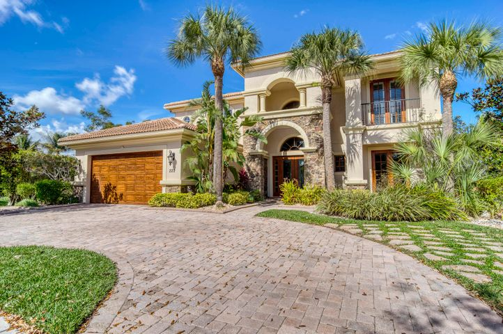 """Exquisite Treanna model situated on an oversized (.43 acre), private cul-de-sac lot in the luxury gated community of Jupiter Country Club. This stately 2-story home offers almost 5,000 sf with 6 bedrooms, 5 baths, an office and flexible loft space. This coveted location offers a trinity of lake, preserve & golf course views and no other properties in the rear. Interior upgrades include Saturnia marble flooring, Brazilian Koa wood flooring, granite countertops, crown molding, custom built-ins in closets & pantry, plantation shutters, whole home AV wiring, and central vac with toe kick systems. CBS construction, impact glass and a UV light air purification system make this home energy efficient & provide a healthy environment. The circular driveway and custom impact glass front doors welcome you into the grand 2-story foyer with a circular staircase and floor to ceiling windows with gorgeous views of the backyard. A private downstairs wing offers 2 guest rooms & full bath. The cabana bath is conveniently located off the family room which is adjacent to the gourmet kitchen. The office is outfitted with a built-in desk & cabinetry, and French doors leading to its own covered porch. 2 separate staircases lead upstairs to the well-laid out split floorplan. A flexible loft space is perfect as a game room, exercise area, media room or additional office area. 2 guest rooms share a Jack & Jill bath and 1 guest room has a private bath & balcony. The owner's suite is expansive with a sitting area, 2 large walk-in closets and French doors opening up to a large private balcony overlooking the stunning vistas. The master bath is spa-like with an oversized whirlpool soaking tub, dual vanities, large walk-in shower & separate water closet. The outdoor oasis boasts a sizeable pool & spa with waterfall, covered lanai, and mature tropical palm trees. Landscaping highlights include various fruit trees including the """"cocktail collection"""" (lime, lemon, orange & grapefruit). The pie-shaped"""