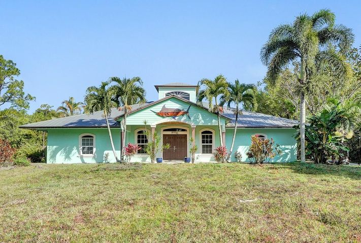 Come see this beautiful 5-bedroom 3-bath CBS home on a high and dry corner lot, located in Jupiter Farms on 1.25 acres.  You're greeted with high ceilings, laminate floors and a split floor plan you will love.  Owners suite is spacious with tray ceiling and ceramic wood looking tile floors, bathroom with dual sinks, separate shower and soaking tub.  Kitchen boasts beautiful white cabinetry, granite countertops, stainless steel appliances, and a massive center island that's perfect for entertaining.  For the Car Enthusiasts, the property also includes a 1,230 sqft airconditioned garage/shop with car lift.  Metal roof, impact windows, structural upgrades extra insulation and more.  Call today for your personal tour.