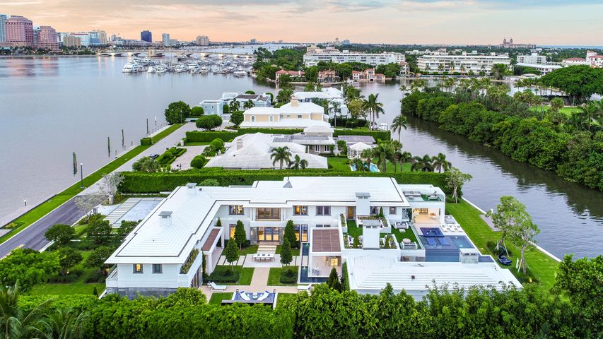 The only new construction direct intracoastal home for sale in the entire Palm Beach Estate Section. Never lived in before, the only modern waterfront home currently for sale on all of Palm Beach Island. One of only two on all of Palm Beach Island with direct Intracoastal frontage and two docks on both the front and back yards.17,190 square feet of total indoor-outdoor living space. Includes $2,000,000 worth of personal property, furnishings, art, sculptures in the listing price. This resort-inspired getaway home, designed by award winning Roger Janssen of Dailey Janssen Architects, is named Lago-a-Lago or Lake to Lake, which aptly describes the property's uniqueness of having Intracoastal frontage on BOTH the front and backyards, each equipped with separate docks, the west dock being over 150' in length. Unlike most of the Palm Beach Laketrail, where the views stare into the abyss, these views across the wide intracoastals anchoring this home are that of the WPB Skyline and Yacht Marina on the west, and Worth Avenue and Everglades Golf Club to the north & east.  The scale of the almost 1 acre, deep site, allowed for the design to accommodate a personal resort-inspired layout with separate suites and living spaces in a fragmented arrangement that weaves together indoor and outdoor spaces. The footprint of the home is built around a very large central courtyard, with pocketing Mahogany wood framed hurricane proof glass sliders from Hartman all the way through, creating a ''see-through'' effect, and allowing views thru both sides of the home to either the west or east Intracoastal Lake at the same time.  There are gravel courtyards and other ornamental grasses, agave, and yucca spread throughout the grounds, opposed to cliche Palm Trees. Lots of different cohesive wood slats, ceilings, and veneers, create an environment which has almost a California feel to it, very unique for South Florida! Inside, a concept of discovery was implemented into this museum-quality finis
