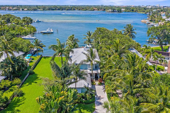 Spectacular views of the crystal-clear blue Loxahatchee River and colorful sunsets await!  This Key West Styled home is on the protected blue water bay along the wide Loxahatchee River, just minutes from the Jupiter Inlet, and is tucked away for your own private tropical cove.  You can paddle board, kayak or cruise right out your back door!   The home features 4 bedrooms, 3 bathrooms, an open kitchen to the family room, large master suite with separate walk-in closets and a spacious covered balcony, pool and lush tropical landscaping.   This charming home on the river won't last! (Outdoor TV and what attached to do not convey. Please note that there is a shared driveway that owner has 50% interest in the driveway which is 25'x142' It is not in the development of Lands End, it is just before you get to lands and on the left side. Boat lift is 12,000 lbs. No pool heater. Tax rolls show Frame construction, wind mit report shows CBS)