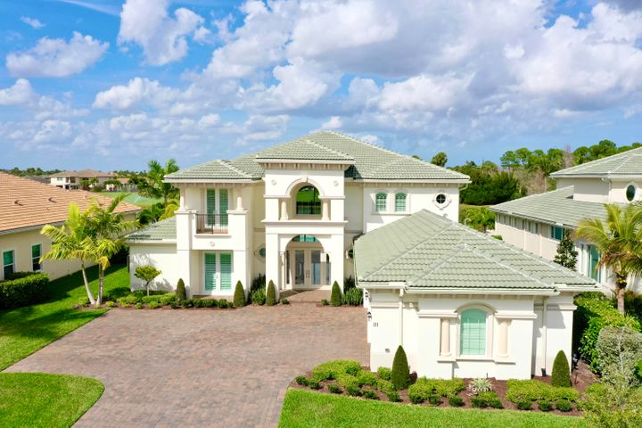 This magnificent home exudes modern sophistication and elegance and is ONE-OF-A-KIND in Jupiter Country Club. Inspired by the Treanna model, the floorplan was customized to suit open concept living and create additional flexible space in the home. The well thought out floor plan features almost 5,700 sq ft of living area, a 3 1/2 car garage, 5 bedrooms, 5 1/2 baths, a loft, a theater room plus an additional flex room that can be converted into a 6th bedroom. Completely customized from top to bottom, superior finishes were chosen to create this luxurious retreat.  Opulent marble flooring flows throughout the downstairs living area. The floor to ceiling windows in the 2-story living room fill the home with natural light. Gather with friends & family in the stunning open concept kitchen featuring an oversized waterfall edge quartz center island. Kitchen highlights include white solid wood soft close cabinetry, a custom vent hood, a marble herringbone backsplash, KitchenAid appliances, a farmhouse sink, a touchless faucet & a wine/beverage refrigerator. Situated on a prime waterfront lot, the panoramic lake & golf course views are breathtaking. Lounge or dine on the expanded covered lanai with travertine pavers and enjoy the glorious sunsets! The outdoor oasis includes the expansive pool & spa which features sparkling turquoise tile and fire & water bowls, a huge lawn area, and mature palm trees & clusia privacy hedges. The divine owner's suite is downstairs boasting 2 walk-in closets, a large sitting area & a spa-like luxurious bath. Also downstairs is a guest bedroom with an en-suite bath and a private porch. The curved staircase takes you the fabulously designed second level. The space is absolutely amazing! There are 3 large guest bedrooms, 1 with a private bath, and 2 with a Jack & Jill bath. A generous loft area overlooks the serene lake & fairway views. Wait...there's more! An additional living area was designed to include an expansive flex/club room PLUS a theat