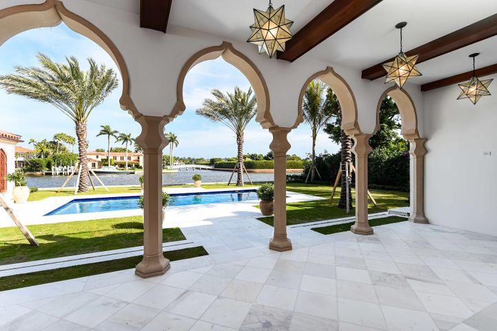 Spectacular waterfront New Construction courtyard home on Everglades Island designed by Smith and Moore. Estate features 7 bedrooms, 7 baths, and two powder rooms. Gorgeous pecky cypress library with fireplace and wet bar. Formal entrance hall with wrought iron curved staircase. Great room with fireplace overlooks Intracoastal. Gourmet top-of-the-line kitchen with butler's pantry opens to waterfront family room. First and second floor owner's suites, elevator, and stunning finishes throughout, including intricate millwork ceilings, elegantly carved stone mantles, and spectacular Moroccan detailing. Fantastic outdoor spaces including tranquil interior courtyard with fountain, several balconies, waterfront loggia, and lakeside pool with cabana. Prime Everglades Island location with gated entry to motor court transports you to your private Oasis. Estimated completion date January 2021.