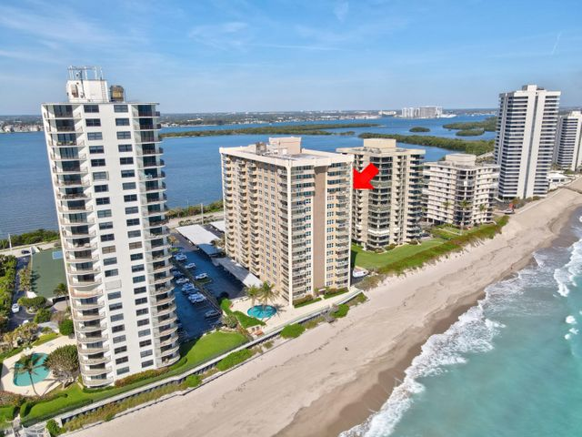 STUNNING OCEANFRONT condo meticulously maintained and renovated to perfection!Located in Aquarius Condo, one of the best maintained (and PET FRIENDLY) buildings in Singer Island, this corner unit has complete wrap around balcony with both intracoastal and ocean views from every room! Rarely available and fully renovated with Spanish tile throughout, there are numerous extras and upgrades that make this one of a kind! Custom open kitchen boasts beautiful rich wood cabinets defined by intricate crown molding, granite counter tops with large island, stone backsplash, Jenn-Aire and Bosch stainless steel appliances, single bowl sink and TONS of cabinets. Living room has smooth ceilings, custom wet bar and sliders that lead out to private balcony with spectacular ocean views. Expansive master suite with walk-in closet and built-ins. Renovated master bath with large vanity, granite countertops, new fixtures, LED lighting, huge walk-in shower with frameless glass shower door, dual shower heads and custom cut-outs. Spacious guest bedroom with plenty of closet space. Guest bath completely renovated with new custom vanity, granite counters, and sliding frameless glass door for both shower/tub combo. LG Front Load washer and dryer nestled into its own laundry closet for added convenience.  This PICTURE PERFECT condo has desirable NE exposure with modern features including glass tempered railings on balcony, full hurricane impact windows and doors, extra storage closet and covered parking. Building recently completed all concrete restoration, along with elevator and parking lot improvements.