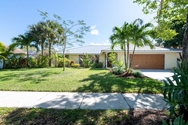 Well maintained single story home in the sought after community of The Shores in Jupiter. 4 bedroom, 3 bath, 2 car garage pool home with beautiful lake view.  A/C 2017, New duct work 2019, Pool resurfaced 2017, Propane gas available, Roof 2019, impact sky Lights, Spacious landscaped front yard. Front exterior covered foyer has tongue & groove ceiling, There is also an interior foyer. There are laminate wood floors in living room, family room and bedrooms. 18''x18'' tile in in the kitchen and breakfast nook.  Living room has  volume ceilings, large bay window and ceiling fan with lighting.  The kitchen has wood cabinetry, a full complement of stainless steel  appliances including a cooktop stove, wall microwave, refrigerator and dishwasher.  It also has a full tile backsplash with tile counters tops and an extended counter bar with plenty of room for seating. The bright breakfast nook has sliders leading to the covered screened lanai and pool area. The large family room has ceiling fan with lighting. and pool view. The dining room has an arched entry, chandelier lighting and sliders for access to the covered lanai. The master bedroom has a ceiling fan with lighting, walk-in closet with shelving, and private entry to the pool and screened patio. The master bath has large single vanity and walk in shower with rain head faucet and crown molding. All three guest bedrooms have ceiling fans with lighting, and reach in closets. One guest bath has shower with floor to ceiling tile. The other guest bath has tub/shower combo with pool and patio access. Both have single vanities. The screened lanai has a long lake view,  and has access to the fully fenced back yard with the pool and spill over spa. There is also a separate laundry room with washer and dryer and 2 car garage with work bench and cabinetry. The Shores is a beautiful community with lakes throughout. Close to beaches, recreation, dining and entertainment. Easy access to major highways and Palm Beach International Ai
