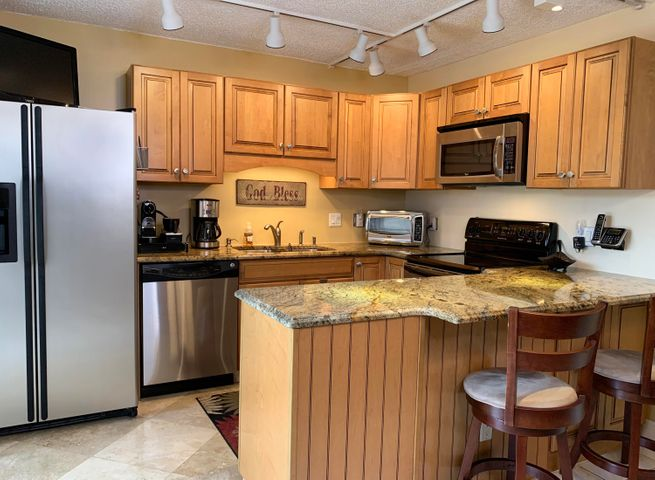 Beautifully remodeled kitchen with custom cabinets, granite countertops with ogee edges, travertine flooring and stainless steel appliances.