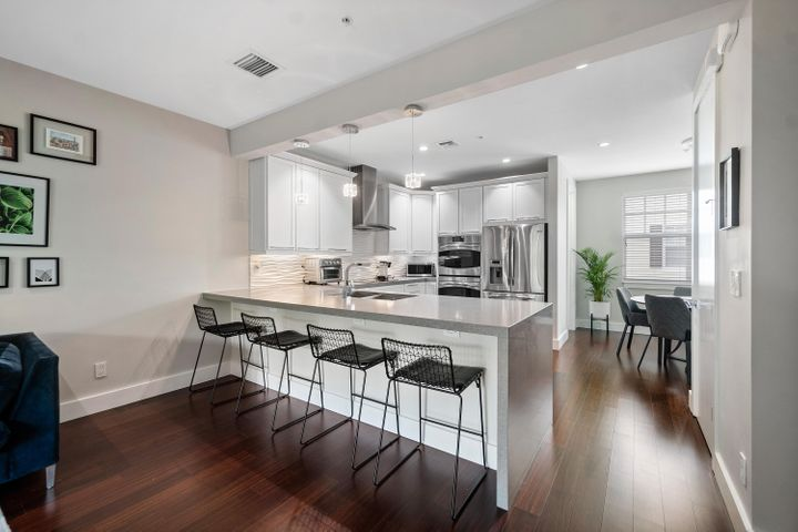 Highly upgraded kitchen with Quartz counters, waterfall feature, and snack bar