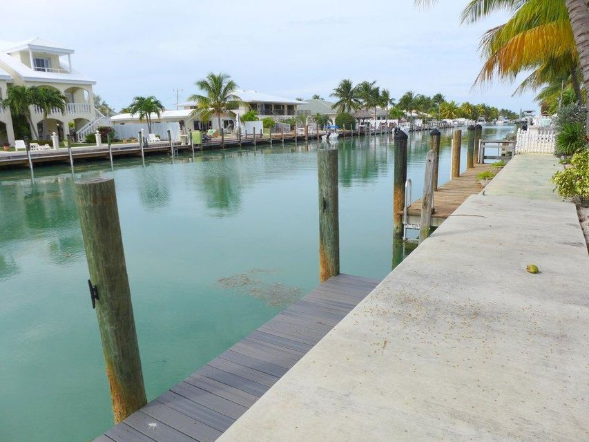 Delightfully updated half duplex with a great location on 9th Street in Key Colony Beach! Easy access to both the Ocean and Gulf side through Vaca Cut Channel.   Great canal views and dock with a concrete seawall and wood step down dock with new surface boards. This 2 bedroom 2 bath home has many upgrades including all hurricane impact windows & doors, all new kitchen appliances, lower cabinets and new counter tops. The master bathroom has been updated and a new instant hot water heater installed. Currently used as a vacation rental so rental history is already in place. Use this as your own vacation getaway, retirement home or investment property. Key Colony offers par 3 golf course, restaurants, Cabana Club, playgrounds, Sunset park and more!