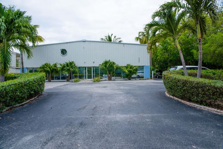 Large commercial building with paved driveway and parking areas