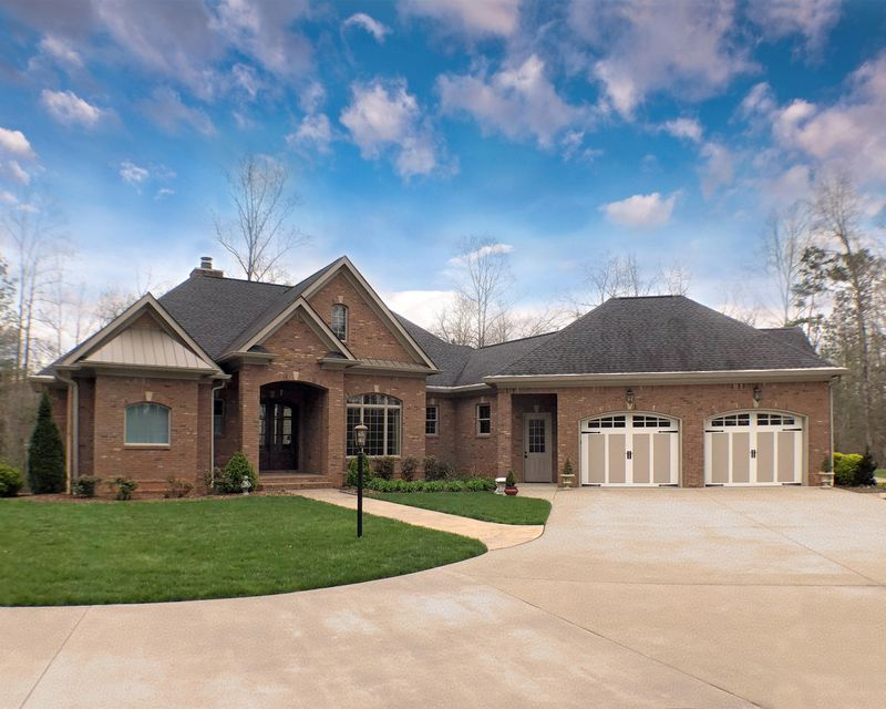 "This owner built, 4,796 sqft, dream home was lovingly constructed using the highest quality workmanship and materials.  Its full brick exterior, gleaming Brazilian Cherry hardwood floors, 8 foot solid wood interior doors and gorgeous window treatments and shades surround an open living space with a 14' ceiling.  Built on 2.5 acres in the prestigious Neuchatel Estates, this home feels like you're entering a newly built home, spotless and virtually untouched by wear and tear.  Enjoy the view through magnificent tall living room windows knowing that the elements won't reach you though the upgraded dual insulated vinyl windows and the 6 inch stud walls. The heart of the home is the custom Ana Woodworks kitchen featuring warm cream cabinets of original design coupled with unsurpassed execution. You'll notice the stylish tile backsplash, the stainless steel appliances featuring a Thermador Gas Range and double ovens, surrounded by its gorgeous granite counter tops. There is lots of beautiful details in the 4"" custom trim and crown molding throughout.  The spacious 2 car garage is on the main level and a 3rd utility garage is on lower level.  Your guests will enjoy the option of 2 powder rooms on the main level.  The generous master bathroom features separate vanities and his and hers walk-in-closets. The walk-out 'daylight' basement offers 2 additional bedrooms and 2 full bathrooms, a family room, and 1102 sqft expansion rooms. Two 80 gallon hot water heaters will ensure you never run out of hot water.  :::: N O T E S: 10 foot ceilings throughout  / 12' ceiling in dining room  / 14' ceiling in the living room with coffered ceiling / Exterior Walls are 6"" studs with R-19 Insulation  :::: H I G H L I G H T S: Ana Woodworks Cabinets 