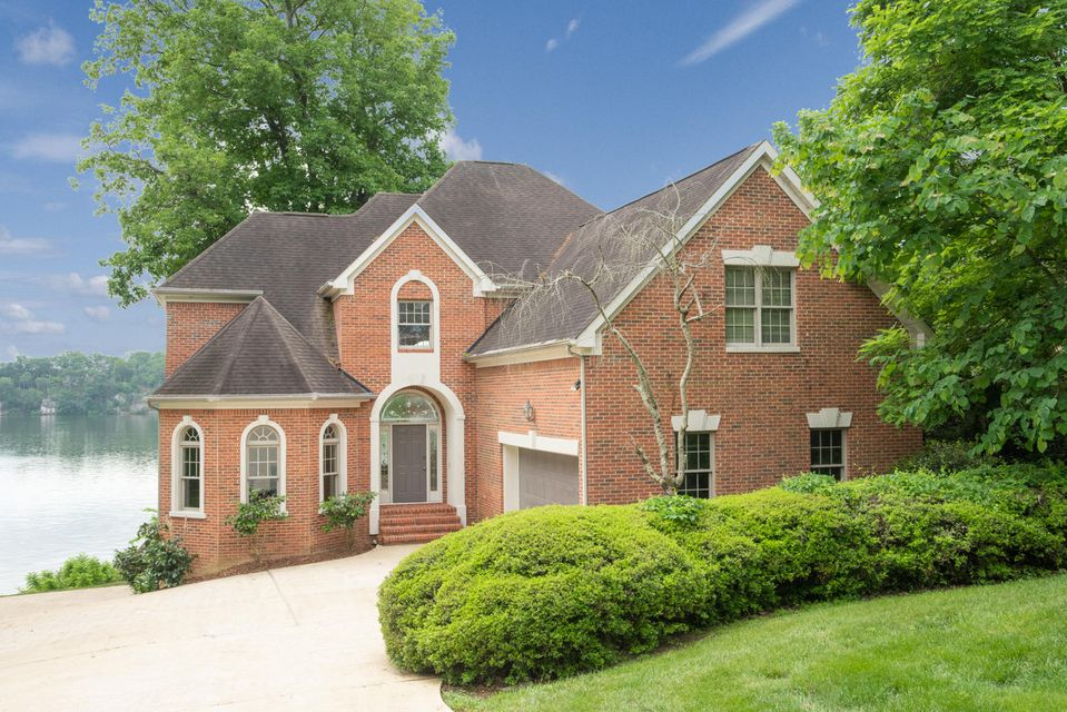 This beautiful all brick home is located in the gated community of Oak Cove. With 125ft of water frontage, this home embraces everything about what life on the lake entails...private access to the water, breathtaking views, ample outdoor living area, and more. This 2-story home features an open floor plan with 20ft+ ceilings in the living room and floor to ceiling windows. Just down the hall, on the main level, is the master bedroom, which includes a spacious en suite, tray ceiling, and hardwood floors. Making your way upstairs, you will find 3 bedrooms, one with a private bathroom, and an additional full bath. The basement level is over 1,000 sqft. of unfinished potential, perfect for storage as it currently has drywall, concrete floors, and 12ft ceilings. The dock is equipped with a boat  lift and two jet ski lifts. Call to schedule your private showing today!